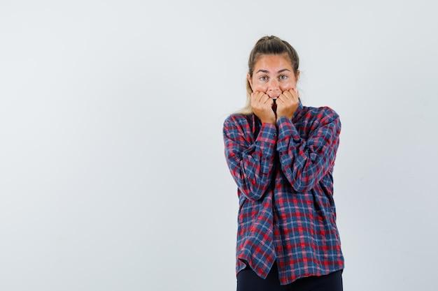 Mulher jovem mordendo os punhos em uma camisa xadrez e parecendo assustada
