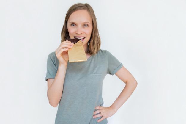 Mulher jovem, morder, barra chocolate, em, folha ouro
