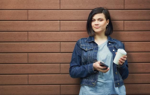 Mulher jovem morena atraente com túneis nas orelhas em uma jaqueta jeans com smartphone em frente a parede de tijolos, desfrutando de seu café quente.