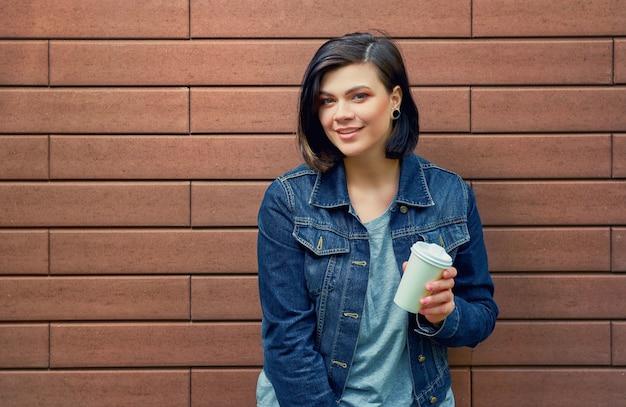 Mulher jovem morena atraente com túneis nas orelhas na jaqueta jeans em pé em frente a parede de tijolos, desfrutando de seu café quente.