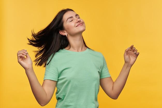 Mulher jovem morena atraente sorridente com camiseta de hortelã mantém os olhos fechados e sente-se relaxada e dançando isolada sobre a parede amarela