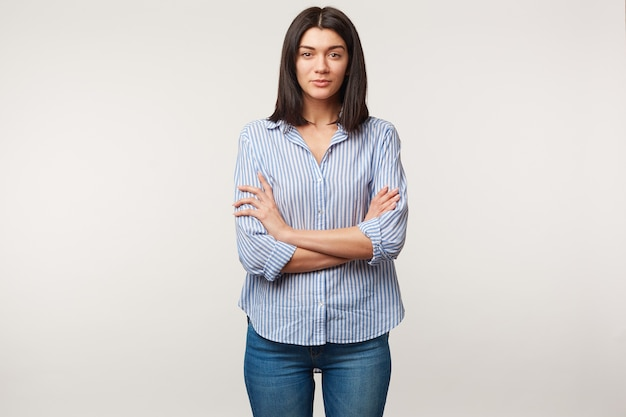 Mulher jovem morena, calma, atenciosa, escuta com respeito, presta atenção, em pé de braços cruzados vestida de jeans e camisa listrada isolada