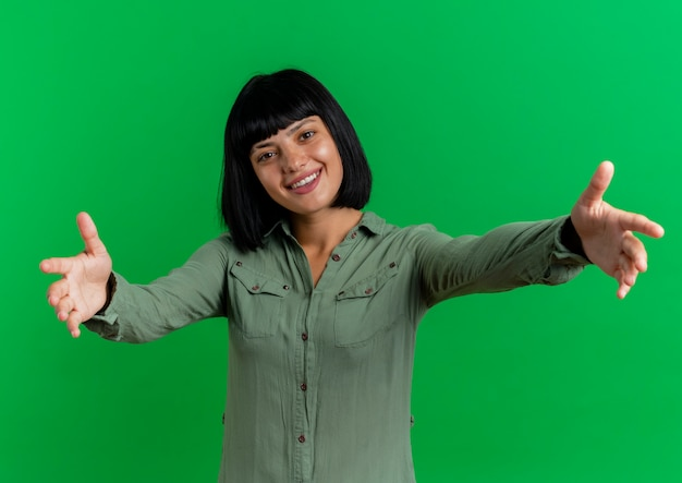 Mulher jovem morena caucasiana sorridente, estendendo as mãos isoladas em um fundo verde com espaço de cópia