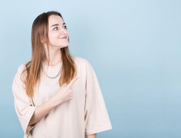 Mulher jovem morena com uma camiseta amarela com uma corrente em volta do pescoço em um fundo azul apontando