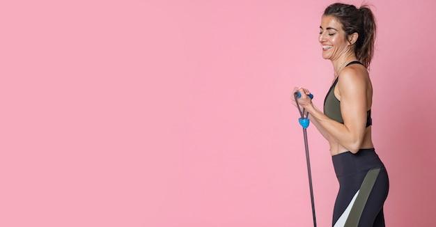 Mulher jovem morena de cabelo com fitness lifestyle training e fazendo exercícios de alongamento com elásticos