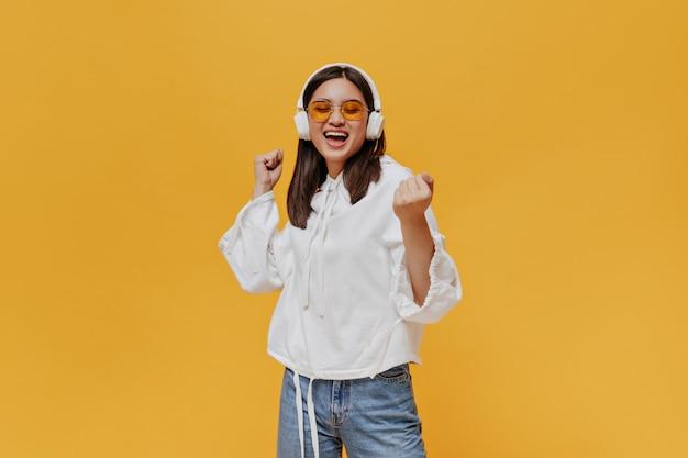 Mulher jovem morena de óculos escuros laranja, capuz branco e jeans canta e ouve música em fones de ouvido na parede laranja