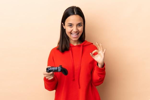 Mulher jovem morena de raça mista, brincando com um controlador de videogame sobre fundo isolado, mostrando um sinal de ok com os dedos