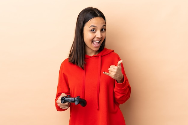 Mulher jovem morena de raça mista brincando com um controle de videogame isolado