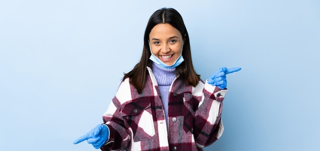 Mulher jovem morena de raça mista, protegendo com uma máscara e luvas ao longo da parede azul, apontando o dedo para as laterais e feliz