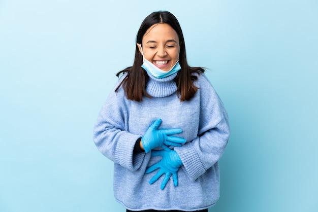 Mulher jovem morena de raça mista, protegendo com uma máscara e luvas ao longo da parede azul, sorrindo muito
