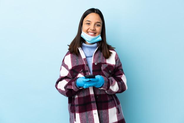Mulher jovem morena de raça mista, protegendo com uma máscara e luvas sobre parede azul, enviando uma mensagem com o celular