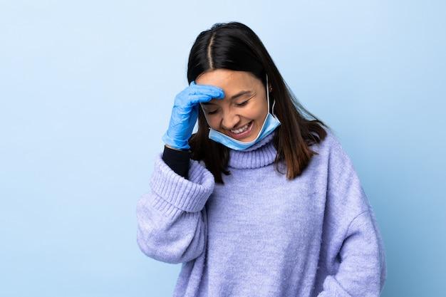 Mulher jovem morena de raça mista, protegendo com uma máscara e luvas sobre parede azul rindo