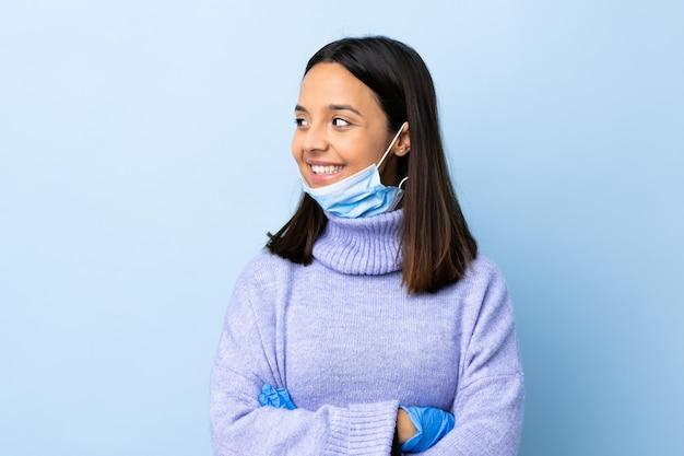 Mulher jovem morena de raça mista, protegendo do coronavírus com uma máscara e luvas sobre parede azul isolada, olhando de lado
