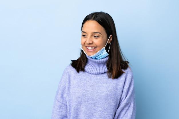 Mulher jovem morena de raça mista, protegendo do coronavírus com uma máscara e luvas sobre parede azul isolada, olhando para o lado e sorrindo
