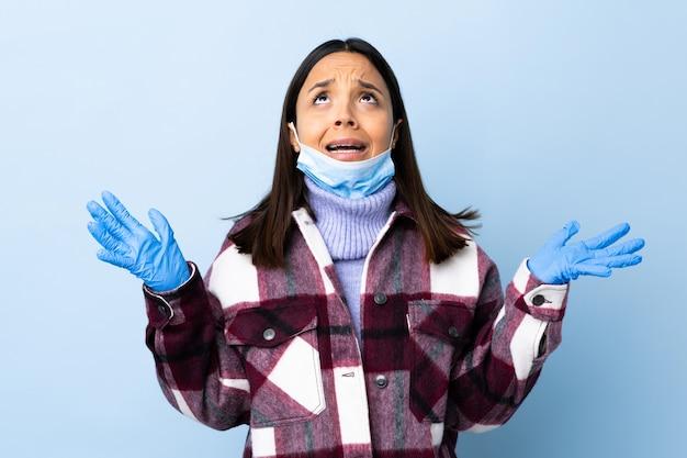 Mulher jovem morena de raça mista, protegendo-se do coronavírus com uma máscara e luvas sobre parede azul isolada estressada oprimida