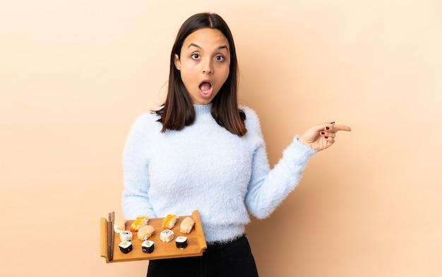 Mulher jovem morena de raça mista segurando sushi isolada surpresa e apontando o dedo para o lado