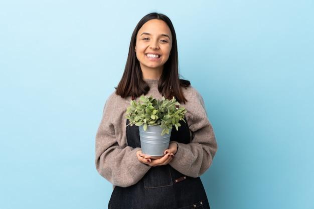 Mulher jovem morena de raça mista segurando uma planta isolada