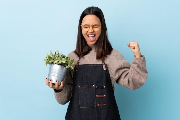 Mulher jovem morena de raça mista, segurando uma planta sobre espaço azul isolado, fazendo um gesto forte