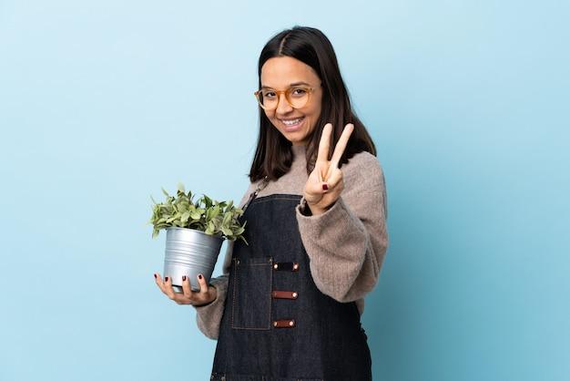 Mulher jovem morena de raça mista, segurando uma planta sobre espaço azul isolado, sorrindo e mostrando sinal de vitória