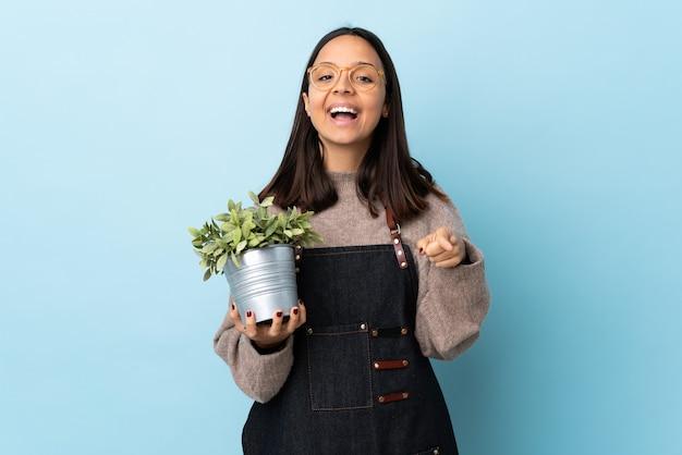 Mulher jovem morena de raça mista segurando uma planta sobre um fundo azul isolado