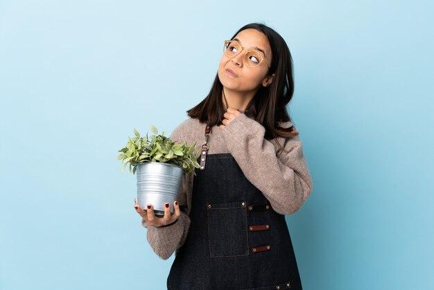 Mulher jovem morena de raça mista segurando uma planta sobre uma parede azul isolada, olhando para cima enquanto sorria.