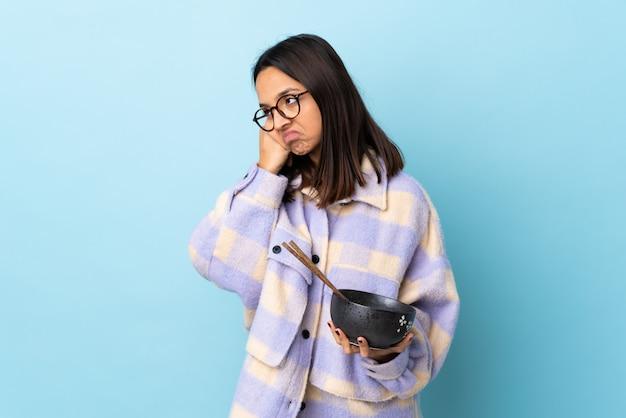 Mulher jovem morena de raça mista, segurando uma tigela cheia de macarrão no azul isolado com expressão cansada e entediada