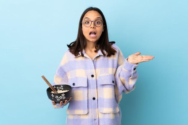 Mulher jovem morena de raça mista segurando uma tigela cheia de macarrão sobre a parede azul isolada, fazendo gestos de telefone e duvidando.