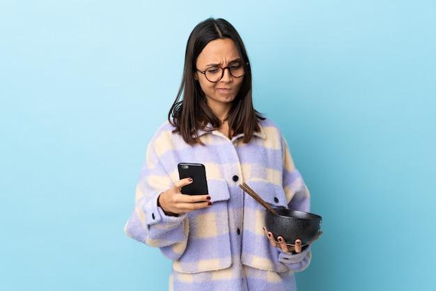 Mulher jovem morena de raça mista segurando uma tigela cheia de macarrão sobre a parede azul isolada, pensando e enviando uma mensagem.