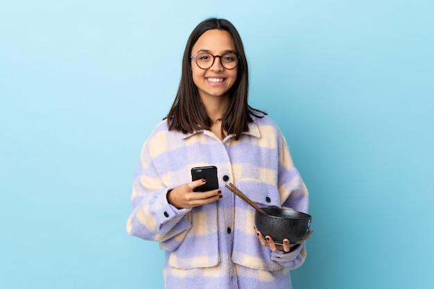 Mulher jovem morena de raça mista, segurando uma tigela cheia de macarrão sobre azul isolado, enviando uma mensagem com o celular