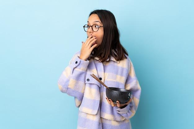 Mulher jovem morena de raça mista, segurando uma tigela cheia de macarrão sobre azul isolado, fazendo o gesto de surpresa enquanto olha para o lado