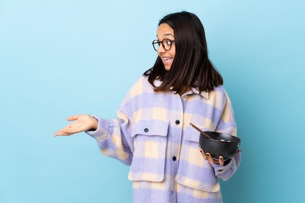 Mulher jovem morena de raça mista, segurando uma tigela cheia de macarrão sobre espaço azul isolado com expressão de surpresa enquanto olha de lado