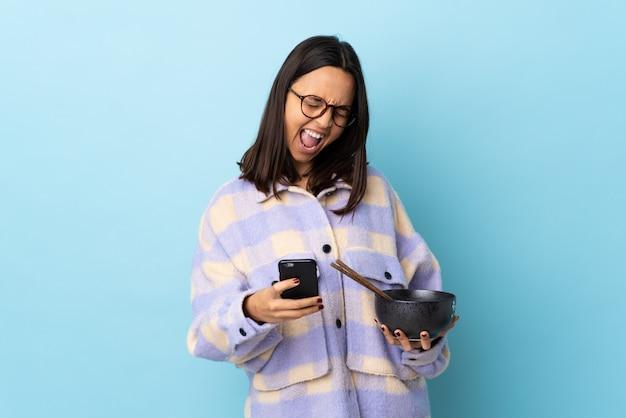 Mulher jovem morena de raça mista, segurando uma tigela cheia de macarrão sobre fundo azul isolado com telefone em posição de vitória