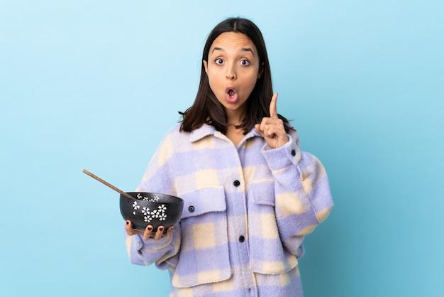 Mulher jovem morena de raça mista, segurando uma tigela cheia de macarrão sobre fundo azul isolado, pensando uma idéia apontando o dedo para cima