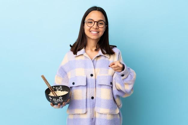 Mulher jovem morena de raça mista, segurando uma tigela cheia de macarrão sobre parede azul, fazendo gesto de telefone e apontando a frente