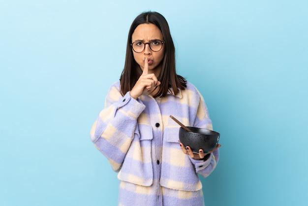 Mulher jovem morena de raça mista, segurando uma tigela cheia de macarrão sobre parede azul isolada, apontando para o lado e fazendo o gesto de silêncio