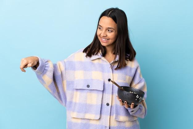 Mulher jovem morena de raça mista, segurando uma tigela cheia de macarrão sobre parede azul isolada, dando um polegar para cima gesto