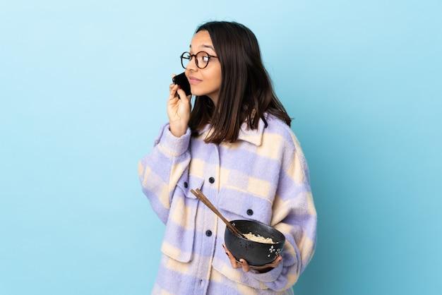 Mulher jovem morena de raça mista, segurando uma tigela cheia de macarrão sobre parede azul isolada, mantendo uma conversa com o telefone móvel com alguém