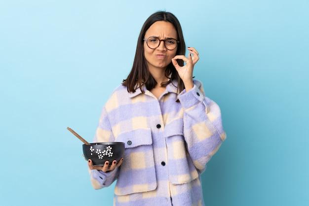 Mulher jovem morena de raça mista, segurando uma tigela cheia de macarrão sobre parede azul isolada, mostrando um sinal de gesto de silêncio