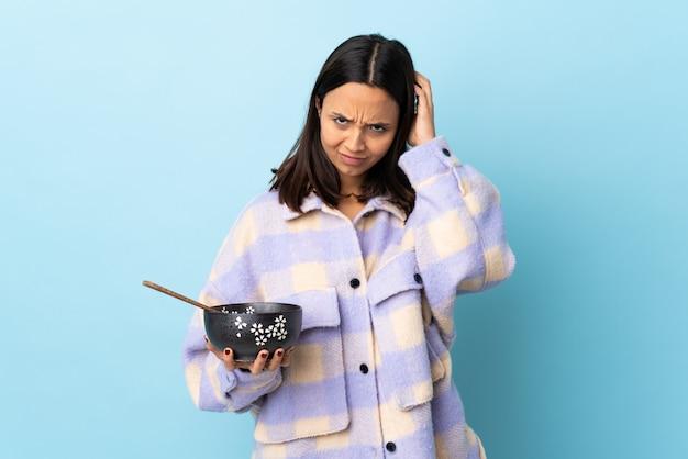 Mulher jovem morena de raça mista, segurando uma tigela cheia de macarrão sobre parede azul isolada, tendo dúvidas