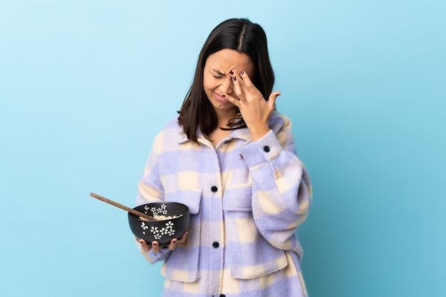 Mulher jovem morena de raça mista segurando uma tigela cheia de macarrão sobre uma parede azul isolada com dor de cabeça.