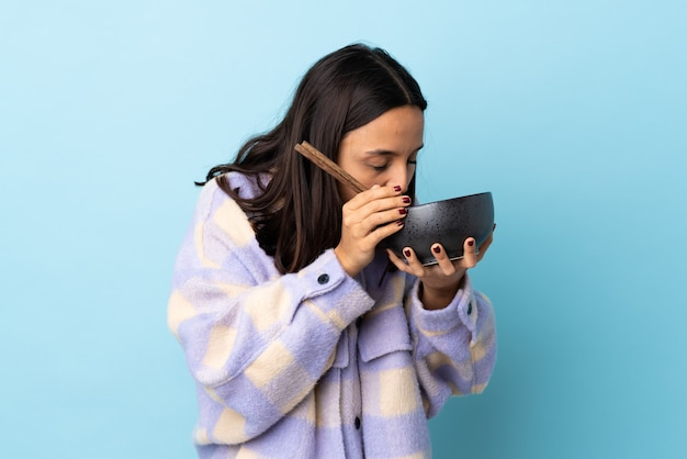 Mulher jovem morena de raça mista sobre espaço azul isolado, segurando uma tigela de macarrão com pauzinhos e comê-lo