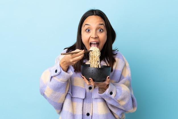 Mulher jovem morena de raça mista sobre parede azul isolada, segurando uma tigela de macarrão com pauzinhos e comê-lo