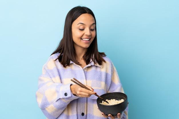 Mulher jovem morena de raça mista sobre parede azul, segurando uma tigela de macarrão com pauzinhos