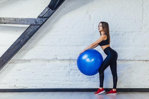Mulher jovem, morena e em forma fazendo aeróbica com uma bola de ginástica