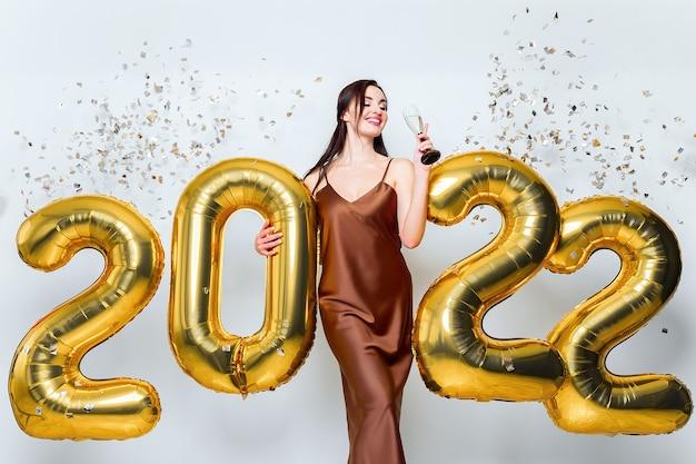 Mulher jovem morena feliz com taça de champanhe perto de balões dourados sobre fundo branco com cl.