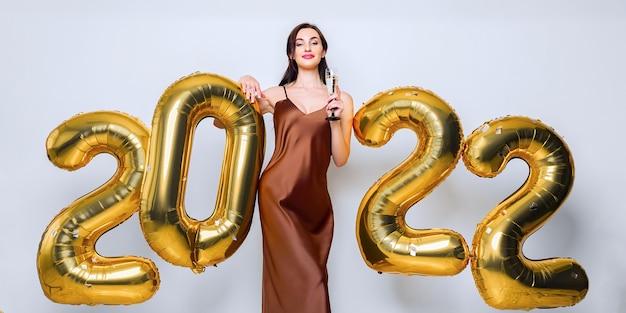 Mulher jovem morena feliz com taça de champanhe perto de balões dourados sobre fundo branco, sim ...