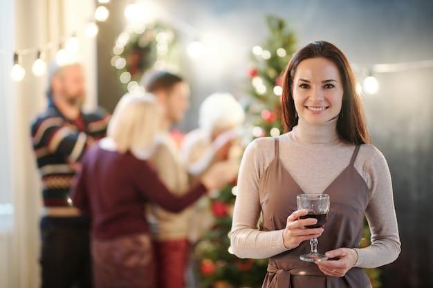 Mulher jovem morena feliz com um copo de vinho parabenizando você no feliz natal com a família dela