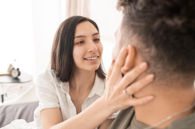 Mulher jovem morena feliz olhando para os olhos do marido com um sorriso gentil enquanto toca seu rosto e deseja-lhe bom dia depois de dormir