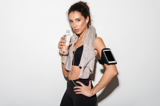 Mulher jovem morena fitness com toalha segurando o braço no quadril