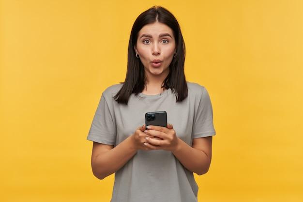 Mulher jovem morena maravilhada e feliz em uma camiseta cinza usando telefone celular e parece surpresa com a parede amarela